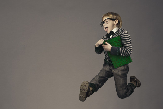 child running back to school funny kid portrait jumping smart schoolboy with glasses and book